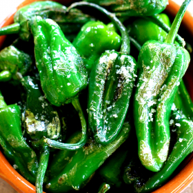 A bowl of cooked Padron peppers